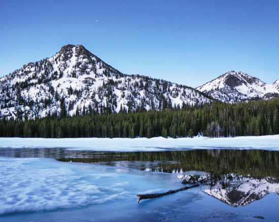 A photo featuring mountain reflections in a partially frozen Anthony Lake.