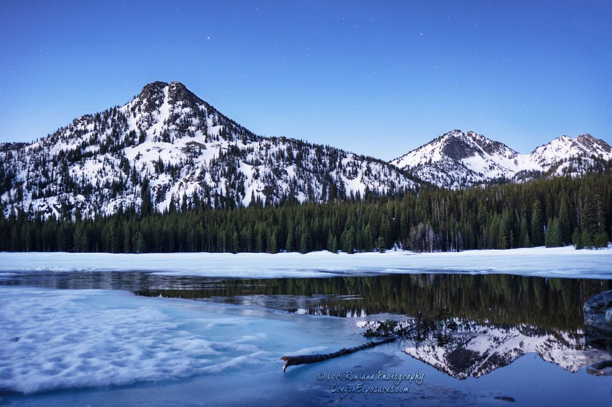 Photo of mountain reflections in the partially frozen waters of Anthony Lake